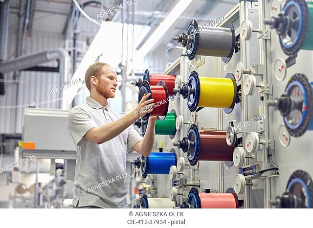 Male worker changing spools on machinery in fiber optics factory