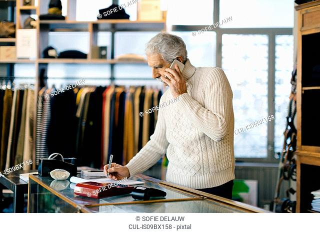 Senior man working in clothes shop using mobile phone