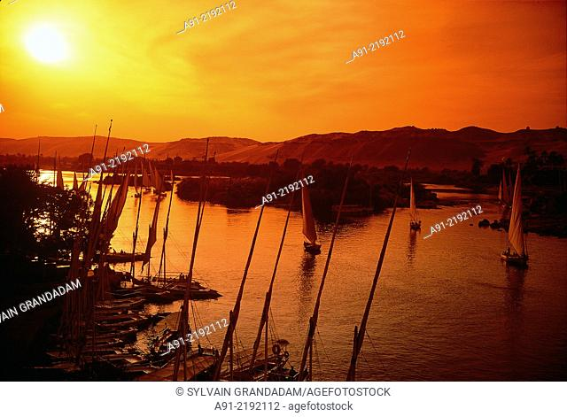 EGYPT.NUBIA.ASWAN.FELUCCAS ON RIVER NILE AT DUSK VIEW FROM OLD CATARACT HOTEL