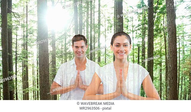 Double exposure of man and woman with hands clasped in forest