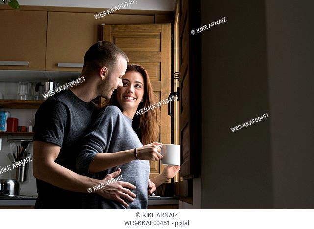 Amorous couple standing in kitchen, embracing with cup of coffee