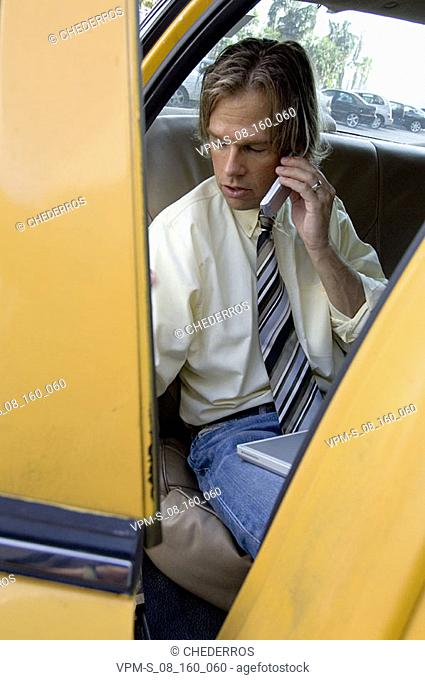 High angle view of a businessman sitting in a taxi and talking on a mobile phone with a laptop on his lap