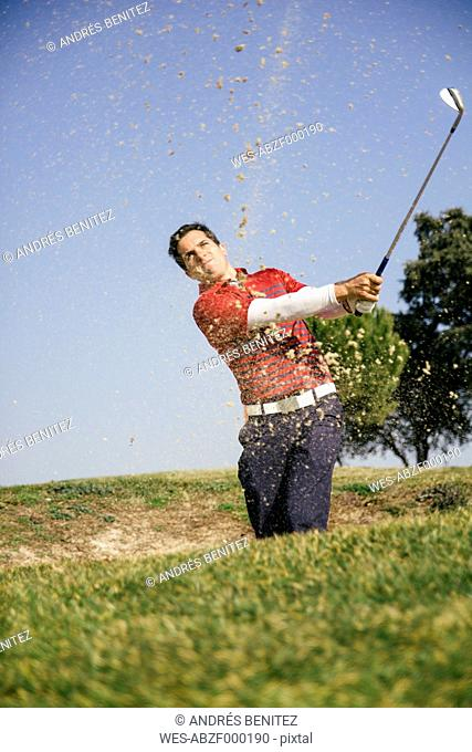 Golfer hitting a golf ball from a sand bunker of a golf course