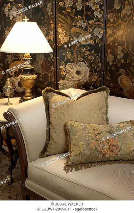 Living room detail of end of sofa with two large pillows, end table with accessories including Buddah head, lamp with ornate base, sitting area, reading area