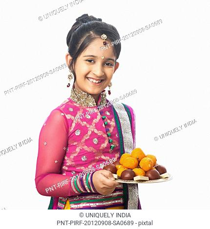 Girl imitating like woman holding a plate of assorted sweets on diwali