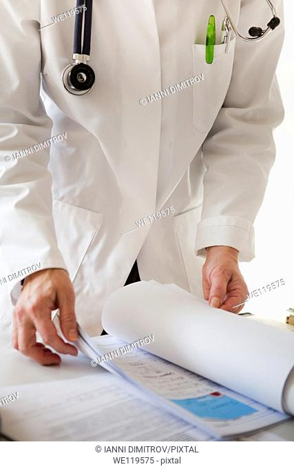 Doctor reading patients file