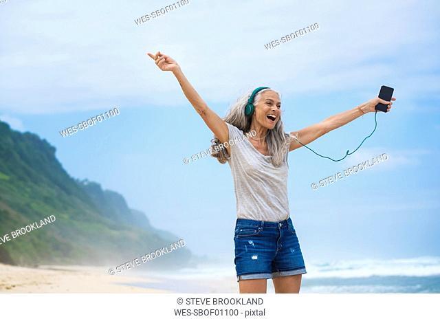 Senior woman with headphones dancing on the beach