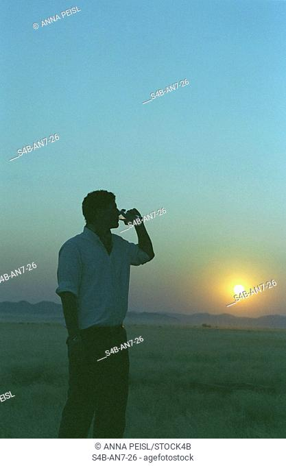 Man drinking from bottle of water, Spitzkoppe, Namibia