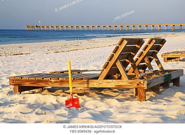Two lounge chairs and a shovel await the next relaxer on the beach in Pensacola, Florida