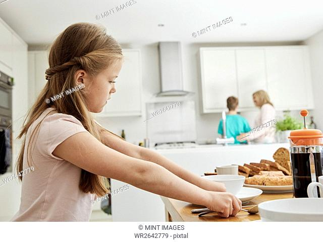 A girl in the kitchen laying the table for breakfast