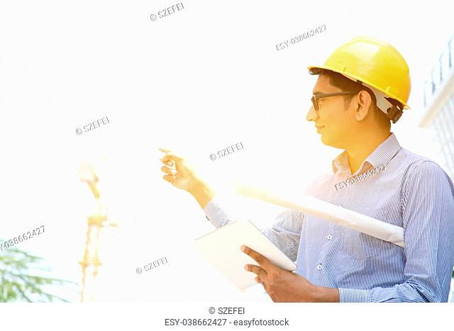 25e3f3e7db9 Asian Indian male contractor engineer with hard hat and tablet pc  inspecting at construction site on