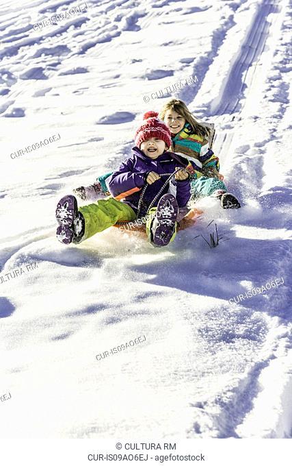 Girls riding sled down snow-covered slope, Achenkirch, Tirol, Austria