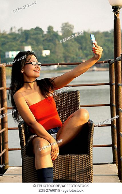 Young woman sitting relaxed on a chair and taking a selfie, Pune, Maharashtra