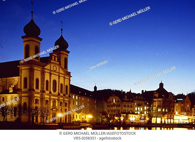 Switzerland, Luzern-City at night with illuminated church and hotel-buildings at the lakefront