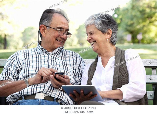 Hispanic couple using cell phone and digital tablet on park bench