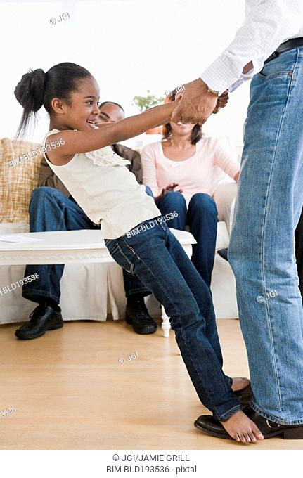 African American father dancing with daughter in living room