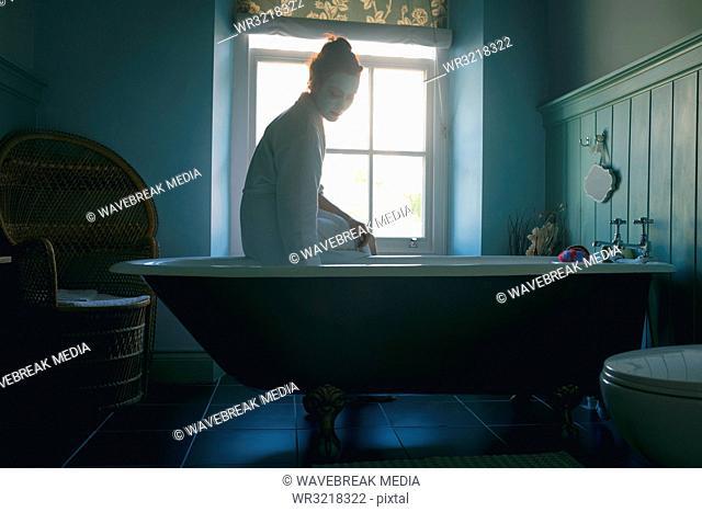 Woman sitting on bathtub checking water in bathroom