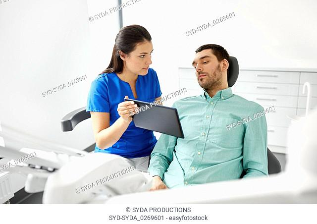 dentist and patient with tablet pc at clinic