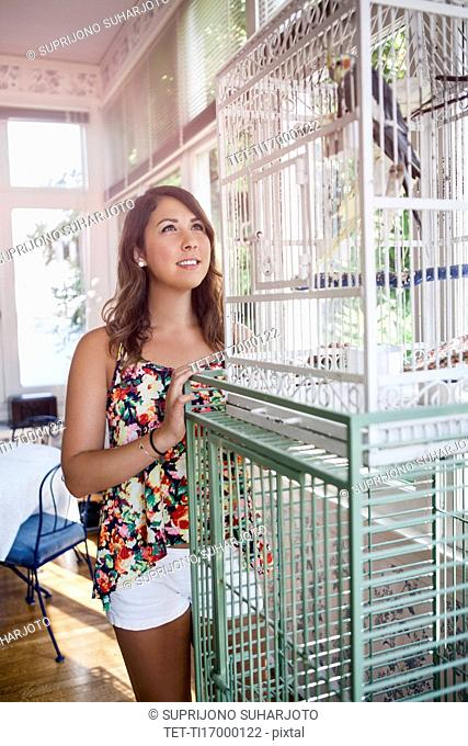 Young woman watching bird in birdcage