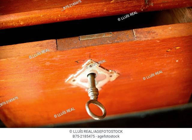 Old open drawer of a cabinet with a key in the lock