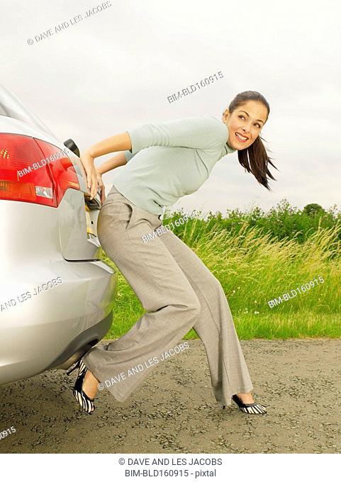 Caucasian businesswoman pushing broken down car on rural road