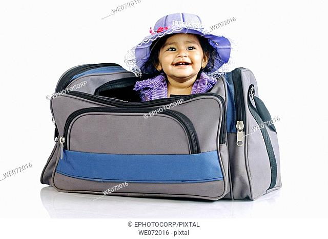 A smiling child sitting in a traveling bag