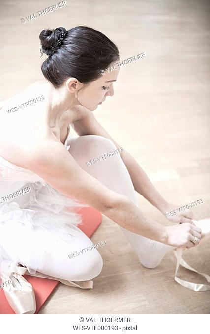 Ballet dancer putting on toe shoes