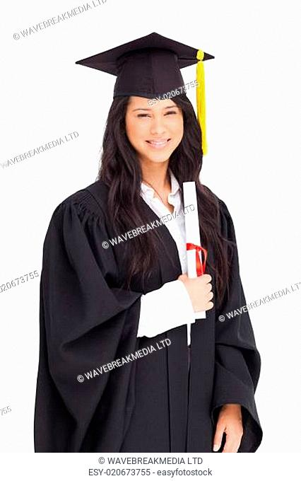 A smiling woman holding her degree as she has graduated from university