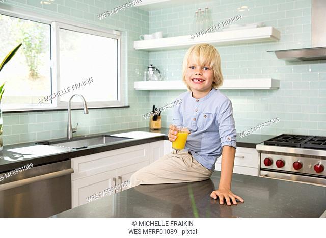 Portrait of happy boy in kitchen with glass of orange juice