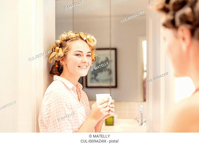 Young woman, foam rollers in hair, holding hot drink, smiling at friend
