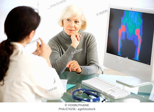 Doctor discussing hip replacement X-ray with a patient
