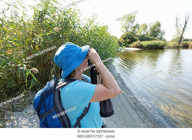 Germany, Usedom, Rankwitz, Lieper Winkel, woman with binoculars watching something