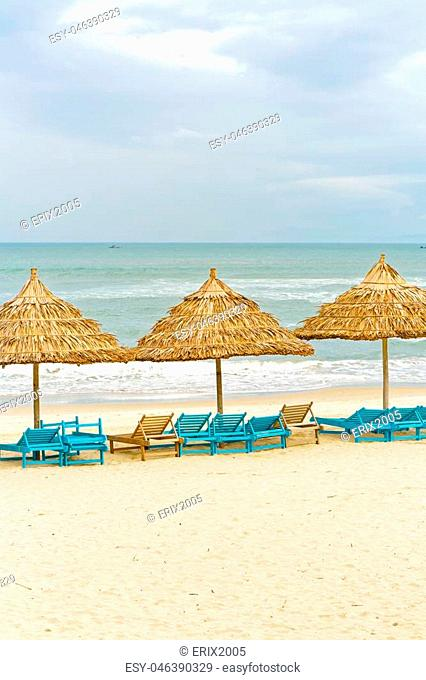 Palm shelters and sunbeds in the China Beach in Da Nang, Vietnam. It is also called Non Nuoc Beach. South China Sea on the background