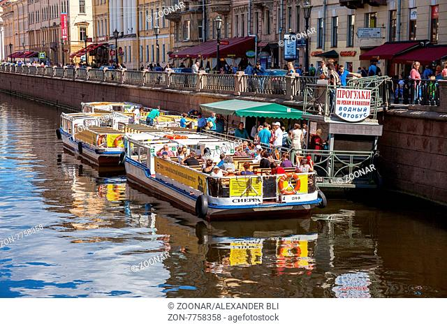 ST.PETERSBURG, RUSSIA - AUGUST 5, 2015: River cruise passenger boats moored on Griboedov channel in the historic city in sunny day
