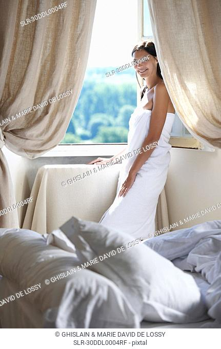 Woman standing by the window in towel