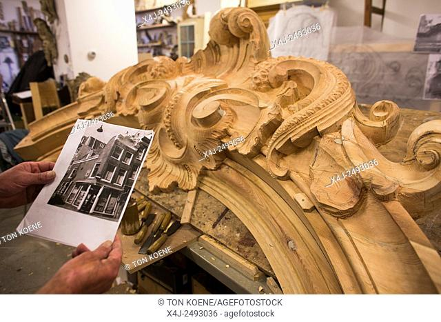 Woodworker making a new house front for a Dutch canal house in Amsterdam