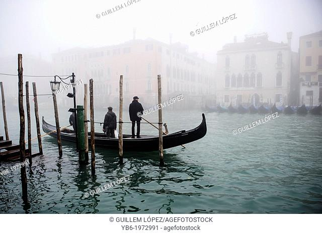 A Traghetto crosses the Grand Canal in Venice covered in thick fog, Italy