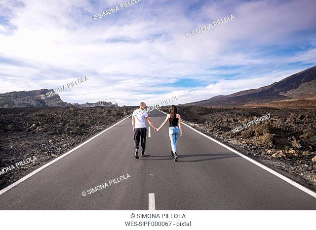 Spain, Tenerife, back view of couple walking hand in hand on empty road at Teide National Park