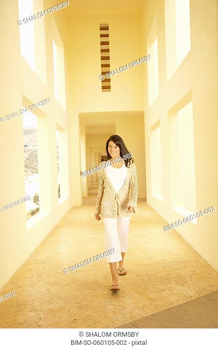 Woman walking down sunlit hallway, Los Cabos, Mexico