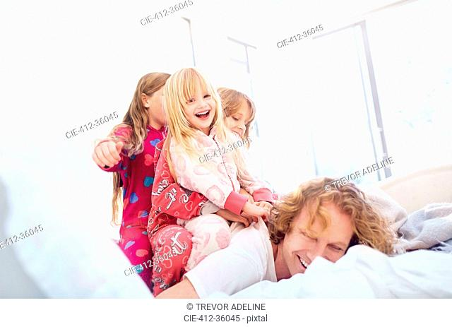 Playful daughters laying on top of father on bed