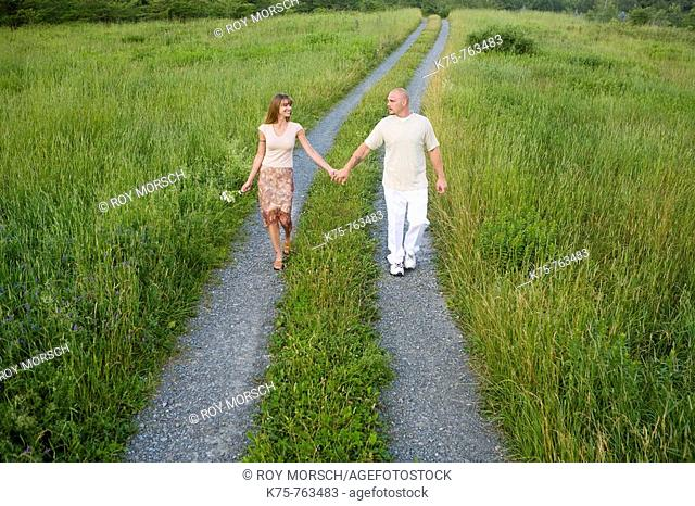 couple walking down country road holding hands