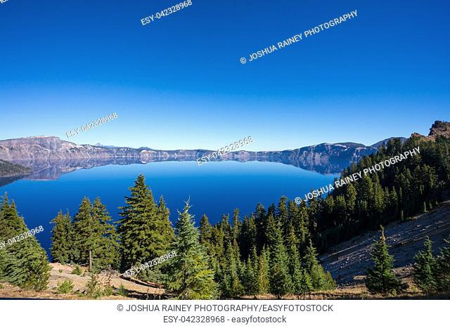 Crater Lake National Park offers beautiful views of the lake with amazing blue water and a few islands in the top of a volcano caldera