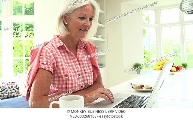 Middle aged woman using laptop over breakfast. Shot on Sony FS700 in PAL format at a frame rate of 25fps