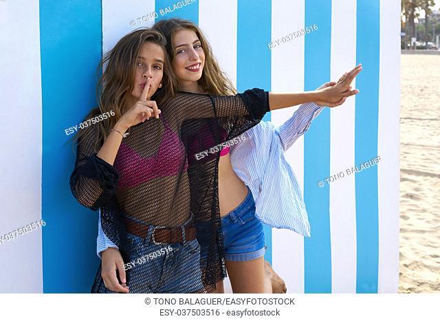 Best friends teen girls silence finger gesture in a summer blue stripes background