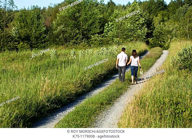Teen couple walking away on country road
