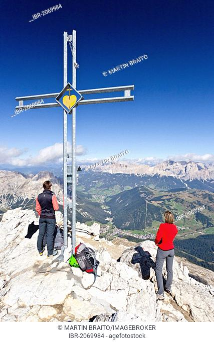 Climbers at the summit cross, Boeseekofel or Piz da Lech via ferrata, Gruppo di Fanis mountains and Mt Heiligkreuzkofel or Sass dla Crusc in the back, Dolomites