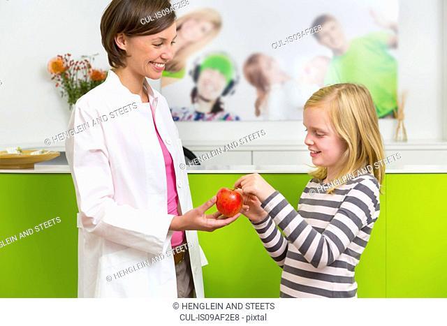 Dentist giving girl apple in dental reception