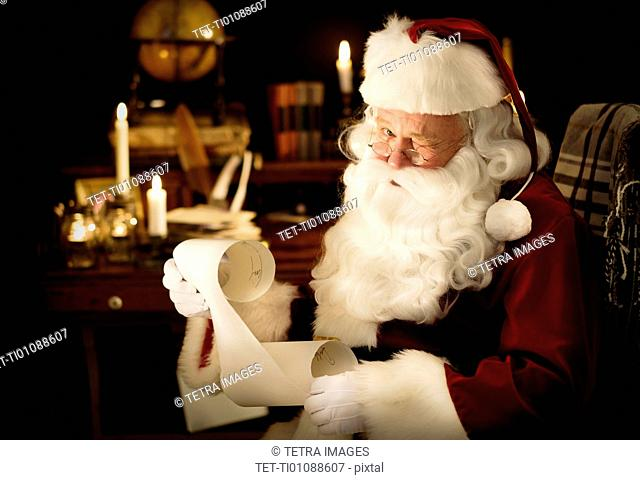 Portrait of Santa Claus reading child's letter and winking