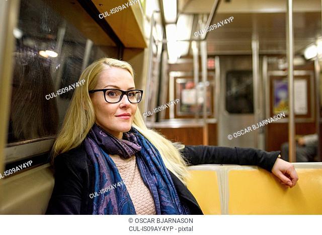Portrait of female tourist on subway train, New York, USA