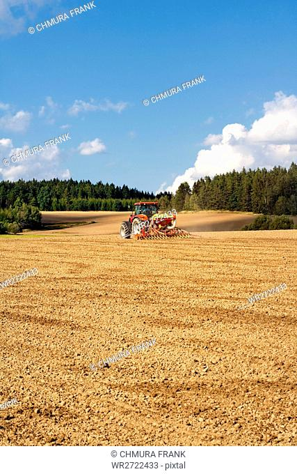 farmer on tractor plowing the field in southern bohemia